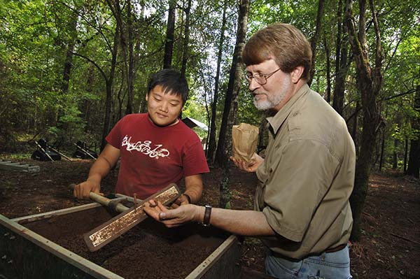 Steve Davis at the home site of UNC founder William R. Davie in Chester County, SC. He is with undergraduate Jiwoo Son, looking at a metal nail from the slave quarters on the property.